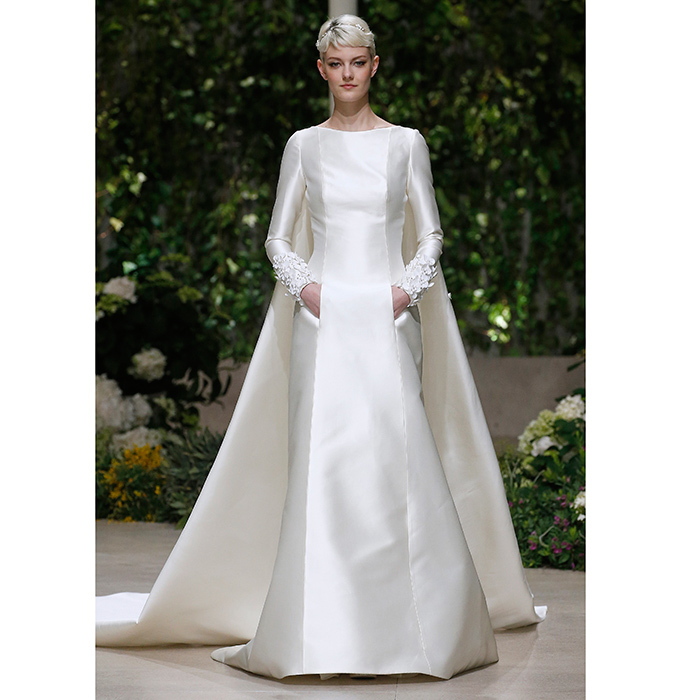 A modest yet modern structured satin look shown on the Pronovias catwalk comes complete with cape and pockets. 