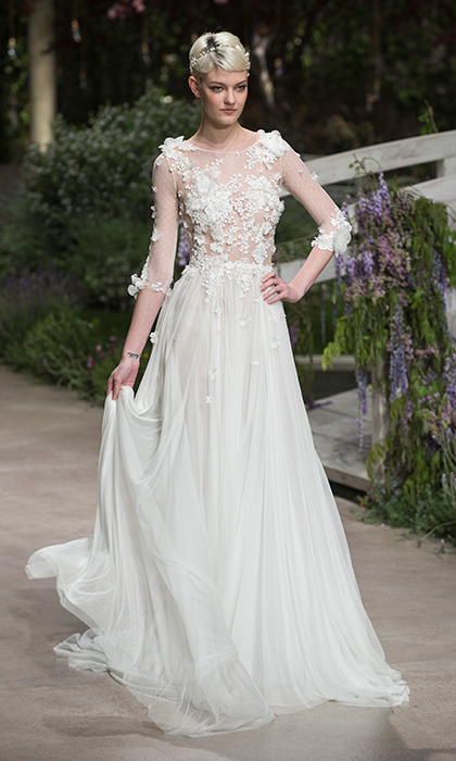 Sheer elegance from Pronovias came in the form of this chiffon number with pleated skirt and appliqué flowers on the illusion bodice and transparent sleeves. 