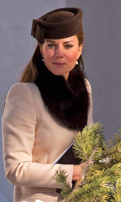 We got to see a rare cold weather wedding look from the Duchess of Cambridge at the March 2013 nuptials of Laura Bechtolsheimer and Mark Tomlinson in Arosa, Switzerland. Then pregnant with son Prince George, Kate wore a simple beige coat with a faux fur scarf and pillbox hat. 