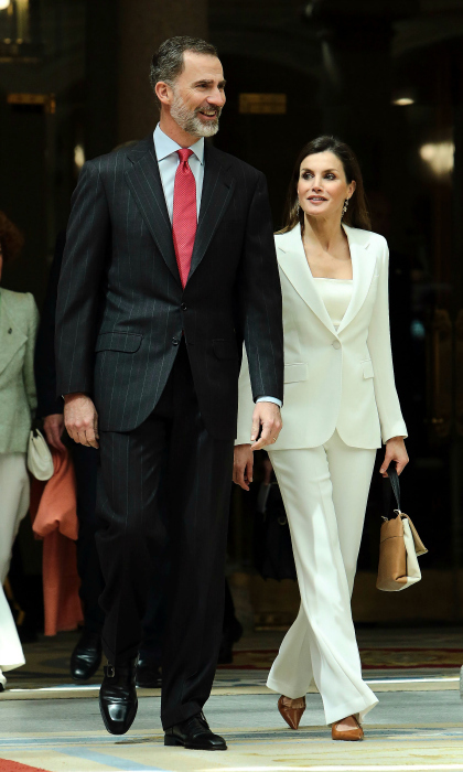 Queen Letizia joined her husband King Felipe VI for an event on May 3 at the royal palace of El Pardo, right outside of Madrid. She had the perfect Spring style for the appearance, opting for a sleek white suit reminiscent of a similar one worn by First Lady Melania Trump only a week prior. She paired the look with a half-camel colored bag.