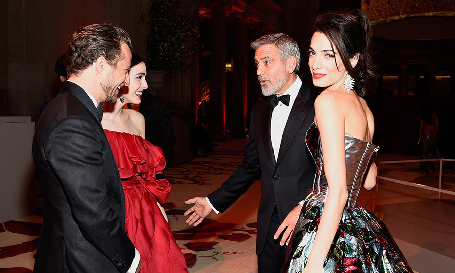 Amal Clooney flashed an over-the-shoulder smile as husband George Clooney chatted with Francesco Carrozzini and Bee Shaffer inside the Met Gala celebration. 