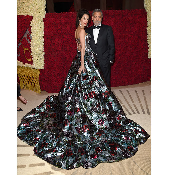 A gorgeous view of Amal Clooney's dramatic floral gown as she posed at the cocktail party with her best accessory – husband George!