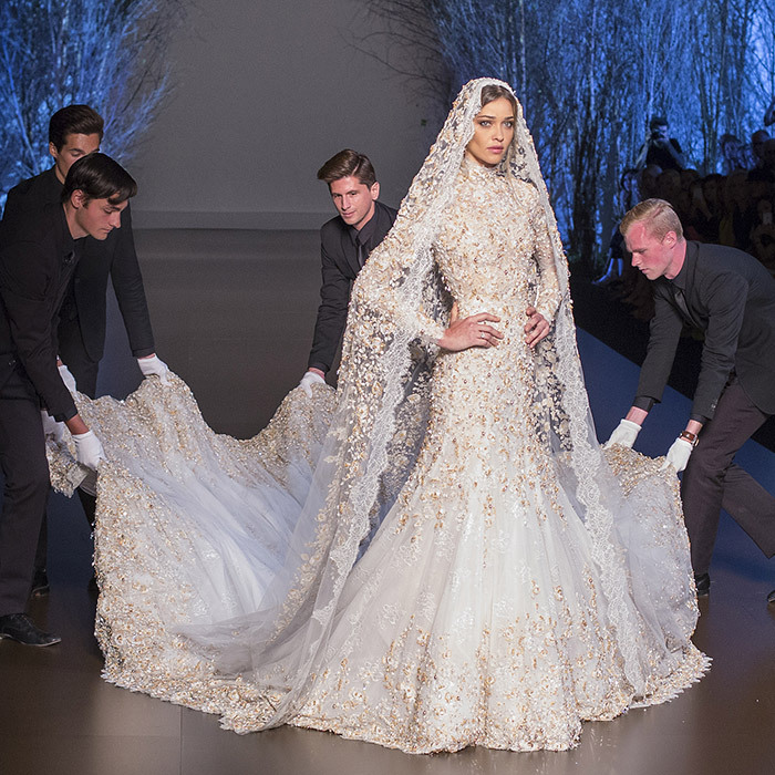 A team helped Brazilian model Ana Beatriz Barros with her train as she modelled this fishtail wedding dress during the fall-winter 2015-2016 presentation. The off-white and silver Chantilly lace gown's cape is hand embroidered with gold and silver crystals, pearls and silk.