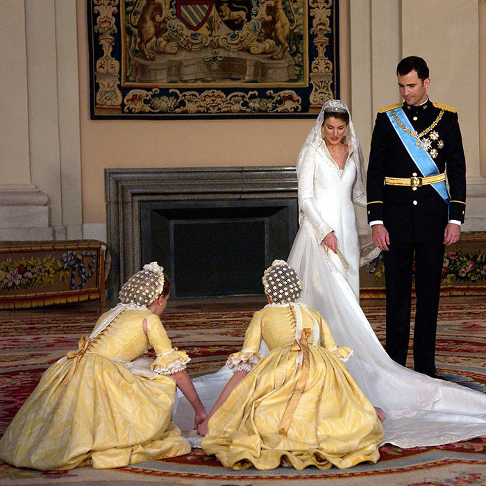 The spring yellow bridesmaids' attire, designed by Lorenzo Caprile, was inspired by the 18th-century works of Spanish artist Goya. Here the two young women are attending to the train of the royal bride's wedding gown before the official photo shoot at the Royal Palace in Madrid.