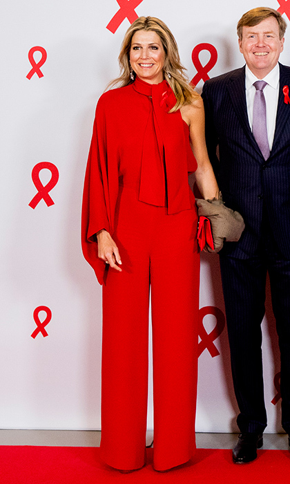 Joined by husband King Willem-Alexander, Queen Maxima of the Netherlands made a bold style statement in a crimson jumpsuit at the Red Ribbon Concert to benefit the fight against AIDS, held in Amsterdam.