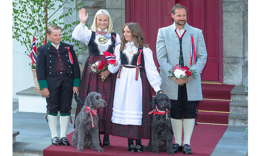 Crown Prince Haakon and Crown Princess Mette-Marit of Norway wore traditional dress along with their kids Princess Ingrid and Prince Sverre outside their home at Skaugum Farm. Their pet dog Muffins and Milly also joined them for the gathering in honor of Norway's National Day on May 17.