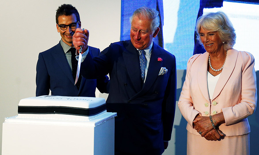 That's not the royal wedding cake! Prince Charles looked like he REALLY wanted a slice as he joined Camilla, the Duchess of Cornwall and Chief Executive of Yoox Net-a-Porter Group Federico Marchetti at the Yoox Net-a-Porter Group offices in London.