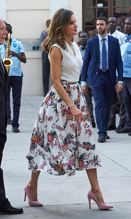 Queen Letizia of Spain donned a 1950s-inspired look with  white wrap top, floral circle skirt and pink pumps for a meeting of Spanish language teachers and students at the Alexandre Petion Liceo on May 23 in Port-au-Prince, Haiti. 
