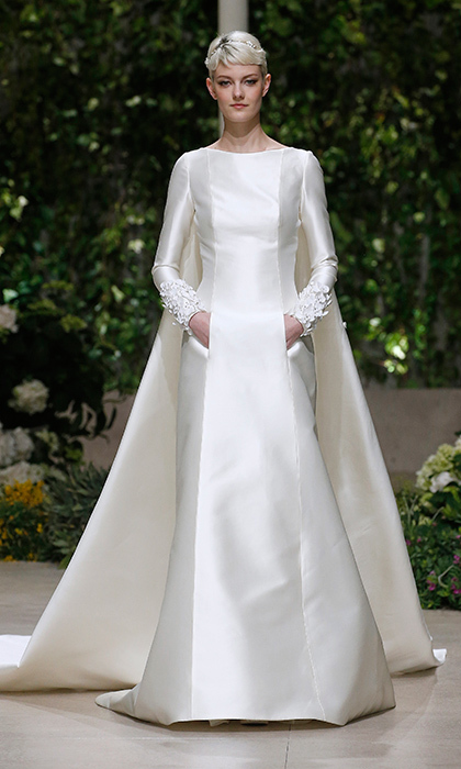 A truly regal mikado look from Pronovias – and it has pockets! The sophisticated gown, with a cape style train, isn't quite flourish free as it has beautiful 3D details just on the cuffs. 