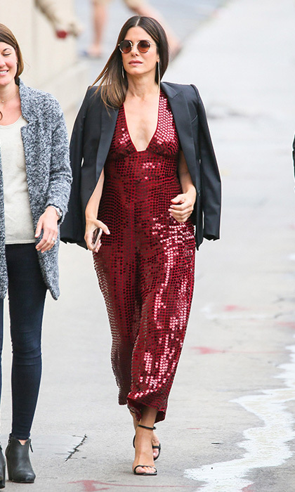 Sandra Bullock cut a very glam figure in a red sequin jumpsuit, tuxedo jacket and shades in Los Angeles on May 30. The actress was on her way to <I>Jimmy Kimmel Live</I>.