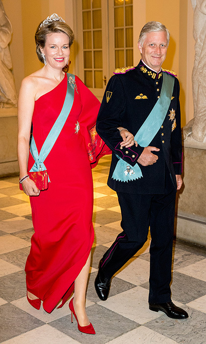Queen Mathilde of Belgium donned a bold red one-shouldered gown for the Crown Prince's 50th birthday. She accessorised with a laurel motif diamond tiara and a red clutch and shoes. 