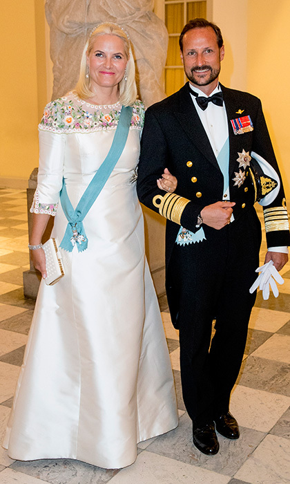 Crown Princess Mette-Marit of Norway, who has been compared to Queen Elsa from <I>Frozen</I>, loves a beautiful white gown! Joined by her husband Crown Prince Haakon, she donne an ivory dress with floral detail for Crown Prince Frederik's soirée. 