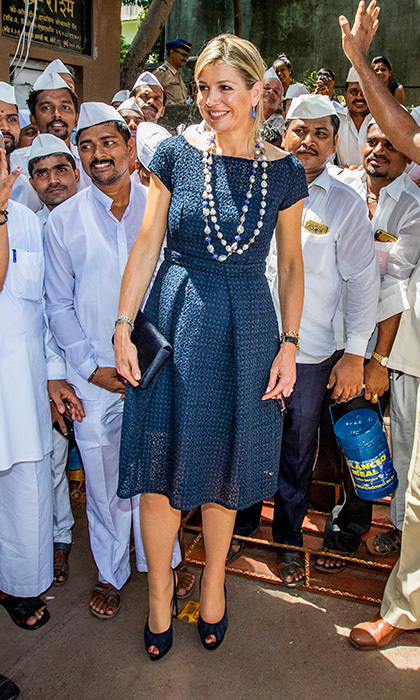 Queen Maxima of the Netherlands wore her signature statement jewellery with a tailored blue day dress as she visited lunch box-carriers, locally known as Dabbawallas, during a 3-day official visit to India.