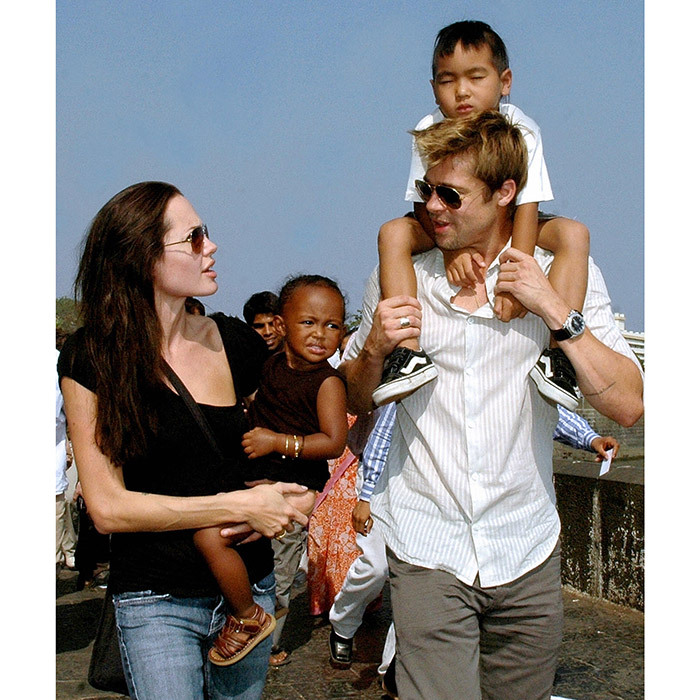 Angelina and then-partner Brad Pitt taking a stroll on the seafront promenade in Mumbai, with Zahara cuddled in her mother's arms and Maddox on dad's shoulders. 