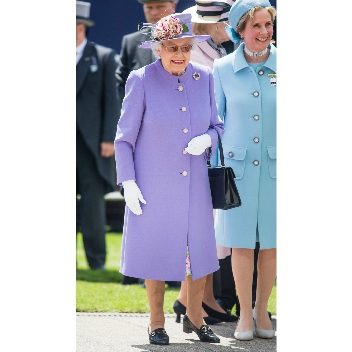 The Queen arrived at Epsom Racecourse with a lovely lilac overcoat and beaming smile.