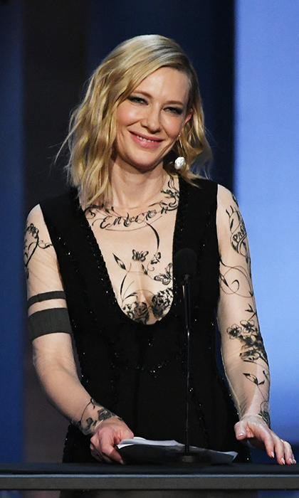 Cate Blanchett also paid tribute to George, drawing some serious fashion attention as well for her tattoo-look dress. The Yacine Aouadi creation has a sheer neckline and sleeves with a cool inked look. 