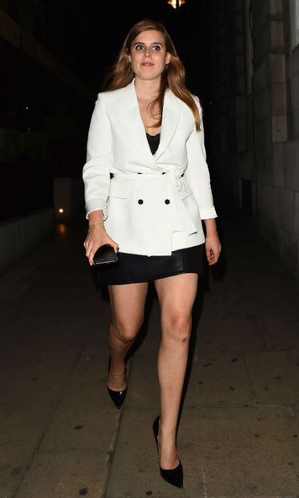 Legs for days! Princess Beatrice stepped out to paint London red on June 9, proving her style credentials once again. The 29-year-old looked fabulous in a fitted white blazer from high street favorite Zara, priced at £89.99 (roughly $120). She teamed the jacket with a black vest top and a patent black leather skirt, drawing attention to her toned legs. To complete her look, Beatrice opted for a pair of black heels, a matching clutch and simple gold bracelets. Beauty-wise, the royal looked lovely wearing her auburn hair down in a bouncy blow-dry and a bold makeup look, which included a smoky eye and a pink lipgloss.