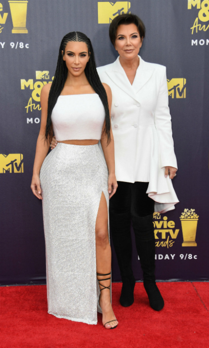 Kim Kardashian West and Kris Jenner had a gorgeous mother-daughter moment on the 2018 MTV Movie & TV Awards red carpet. The reality stars stepped out looking their usual glam selves on Saturday, June 16 at Barker Hangar in Santa Monica, matching in white ensembles. The 37-year-old makeup mogul wore her hair in braids and flaunted a tight tummy in a dazzling Atelier Versace crop top and skirt.