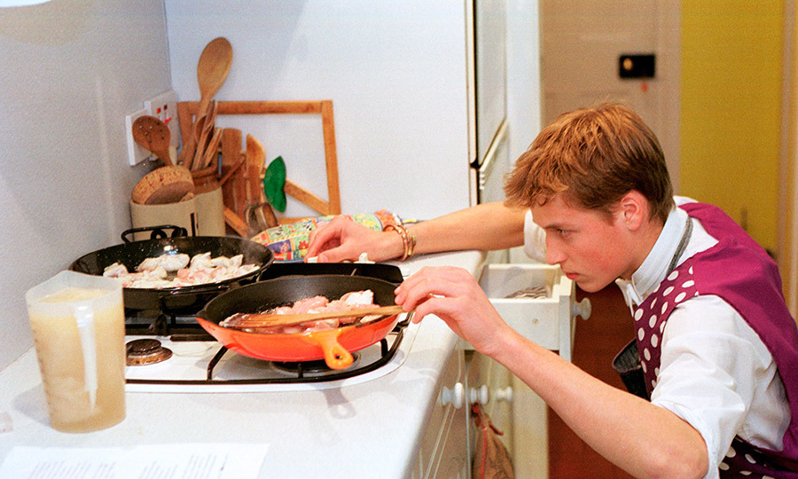 In June 2000, Prince William showed he was picking up more than academic skills during his boarding school days at Eton. Here, the young royal wears an apron and looks fully focused as he whips up some paella in the kitchen.