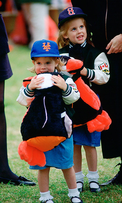There's nothing Beatrice and Eugenie seemed to love more than dressing alike! Here the two adorable girls go casual in baseball caps and varsity jackets in May 1993 at a fairground in Windsor.