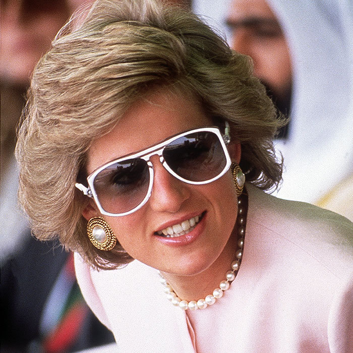 Princess Diana combined couture and sportswear chic in this Catherine Walker suit, pearls and white 1980s sunglasses! The royal was watching camel racing at Al Maqam during an official visit to Abu Dhabi in March 1989. 