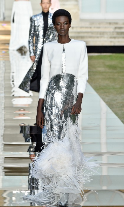 The former <i>Suits</i> star is certainly not one to stray away from capelets. However, this Givenchy original adds some pizzazz to the royal style staple with eye-catching counterparts. The metallic silver sequin gown comes to a mermaid-like bottom which features white feathers.