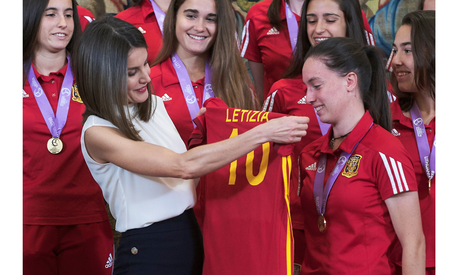"Put her in coach! Queen Letizia received her very own personalized soccer jersey on Thursday, July 5. The Spanish U-17 women's national soccer team, who won the 2018 European title of their category in May, presented Her Majesty with the gift at Zarzuela Palace. The Queen's jersey matched the team's colors of red and gold and featured her named ""Letizia"" emblazoned on the back with the number ""10."" Letizia proudly held up the jersey as she posed for photos with the team and coaching staff.