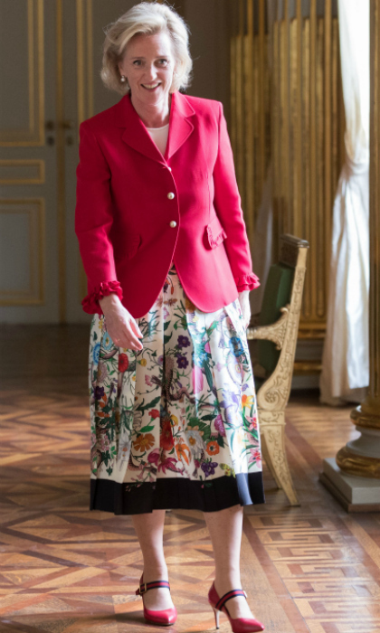 The Princess expertly dressed for the occasion in a red rose-colored jacket and floral print skirt.