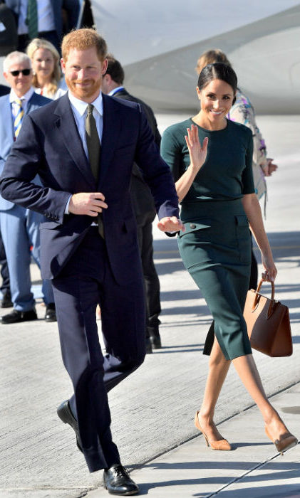 The Duke and Duchess of Sussex made a stunning landing in Dublin on Tuesday, July 10 to kick-start their two-day tour. Meghan looked as stylish as ever, wearing a fitted green shirt and skirt by one of her favorite designer's Givenchy, which she accessorized with Strathberry Mid tote in tan. She kept her hair tied up in a low bun and her makeup natural. Harry, who appeared happy and relaxed by her side, was looking dapper in a suit.