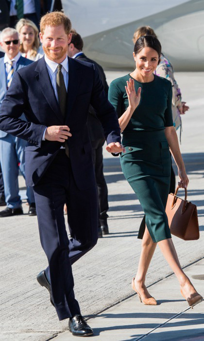 Kicking off the couple's first overseas tour earlier in the day, Meghan wore a fitted green top by one of her favourite designers Givenchy. She teamed it with a co-ordinating skirt that featured side pockets and an on-trend mid-length cut. she accessorised the design with a Strathberry Mid tote in tan, and matching court shoes.