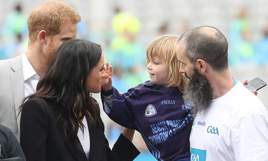 The three-year-old was so smitten that he continued to touch her face, which Meghan didn't seem to mind.