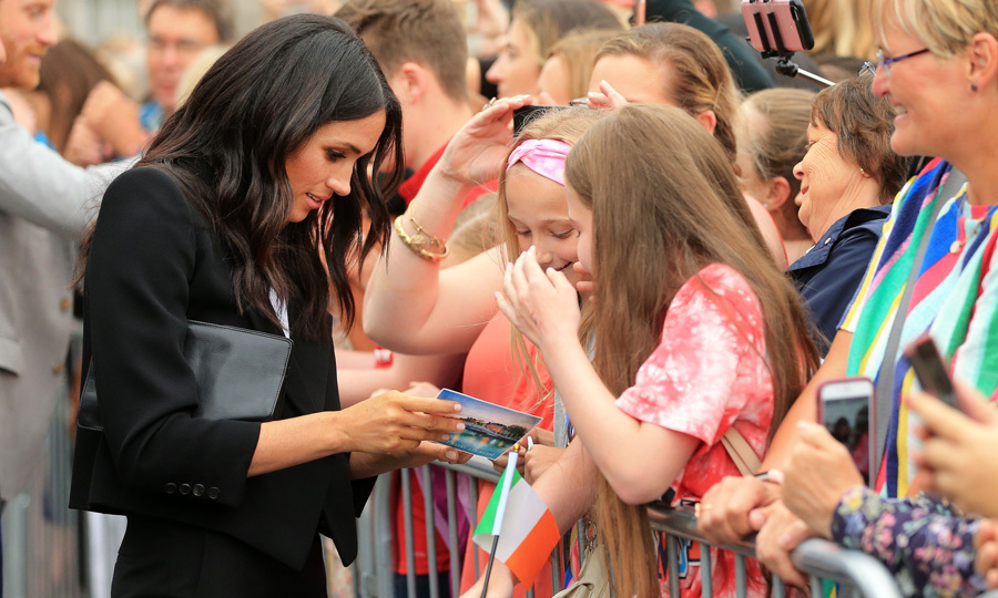 Meghan made a couple of fans happy when she walked over to them and checked out a postcard they had during their visit to Trinity College in Dublin. 
