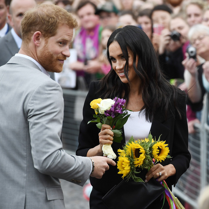 He loves me, he loves me not... Meghan had a nice collection of sunflowers and other flowers that she was given by bystanders on her and Harry's first royal trip as a married couple. 