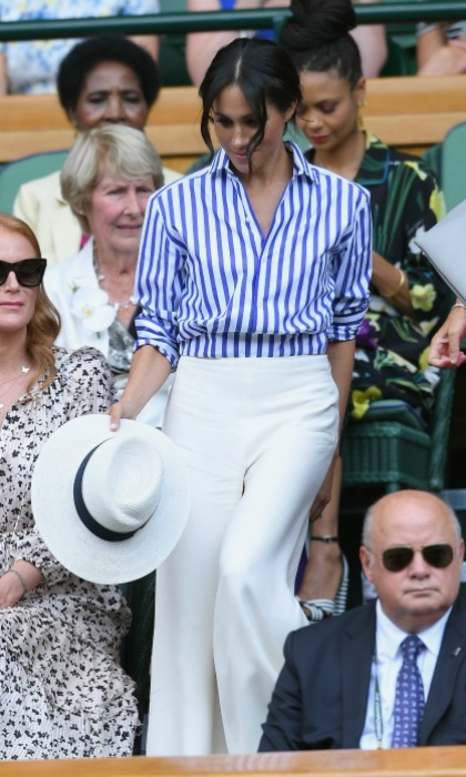 Meghan wore similar-looking high-waisted trousers to the <i>Harry Potter</i> star's summer bottoms. She completed the head-to-toe Ralph Lauren look with a blue-striped shirt and a bag by Alturzarra.
