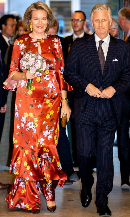 After a week of stylish appearances, Queen Mathilde managed to thrill fashionistas everywhere yet again as she arrived to the Prelude to the National Day Concert at Palais des Beaux-Arts on July 20 in Brussels, Belgium with her husband King Philip. The 45-year-old royal sizzled in a burnt orange satin gown that featured a high neckline with a teardrop opening in the center. 