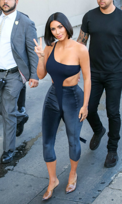 Peace and selfies! Kim Kardashian flaunted a tiny figure in a unique looking velvet ensembles while arriving at <i>Jimmy Kimmel Live</i> on July 30 in L.A. 