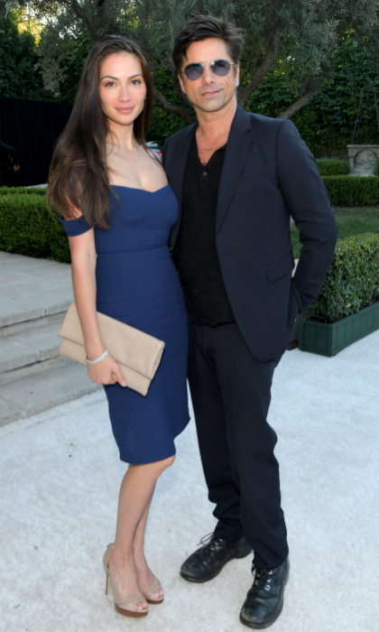 Date night! John Stamos and his wife Caitlin McHugh left their baby Billy at home as they stepped out to represent <i>Fuller House</i> at the star-studded Netflix event. The 55-year-old new dad looked sharp with his shades on in a dark suit ensemble, while his love Caitlin rocked royal blue.