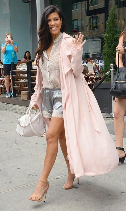 Teaming satin shorts with a loose blouse and long pale pink coat while out and about in New York.