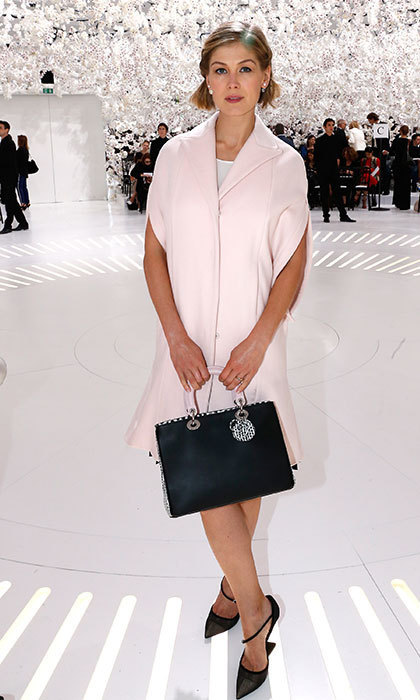 In a pale pink outfit with a black Dior bag and matching black stilettos for the fashion house's haute couture show in Paris.